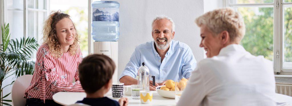 Familie mit Kind sitzt zusammen mit Wasserspender im Hintergrund.
