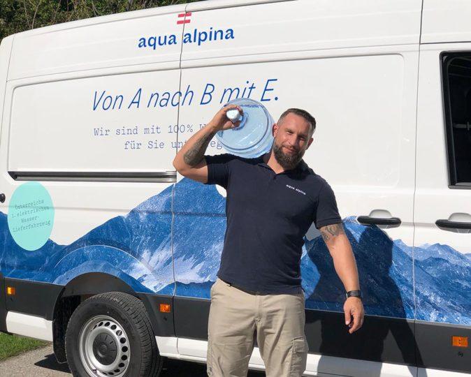 Servicefahrer mit Wasserflasche vor einem Elektroauto