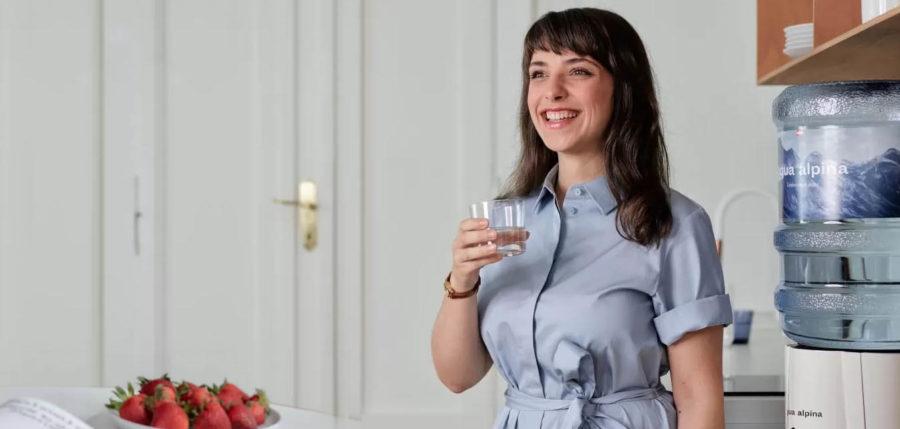 Frau steht vor Wasserspender und trinkt