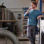 Mitarbeiter Trinkt In Produktionshalle Von Festwasserspender