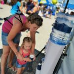 Familie trinkt vor Wasserspender