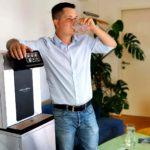 Leitungsgebundener Wasserspender Soda Premium Mitarbeiter Trinkt aus Wasserglas