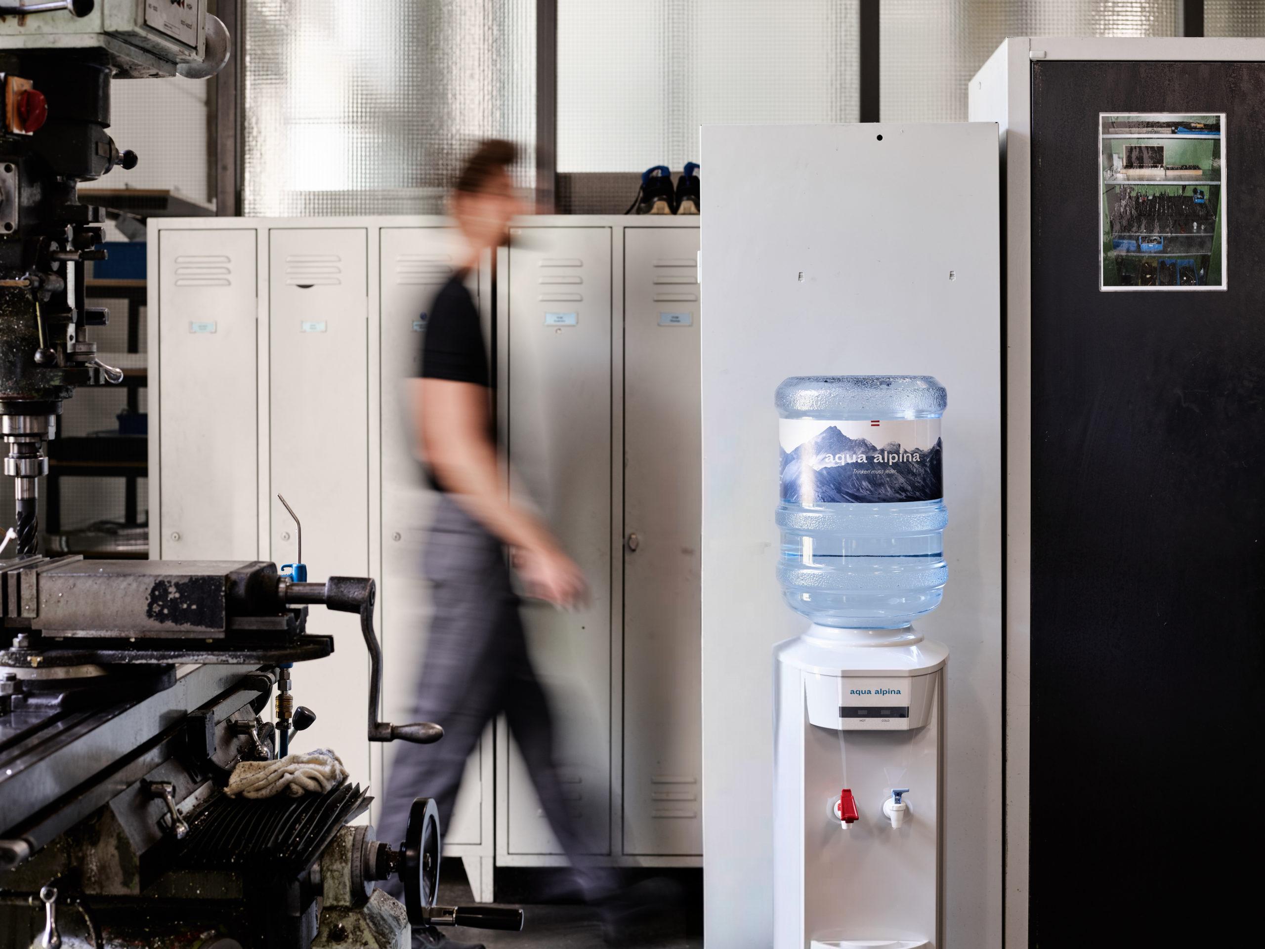 Produktionshalle Person Geht An Wasserspender Vorbei