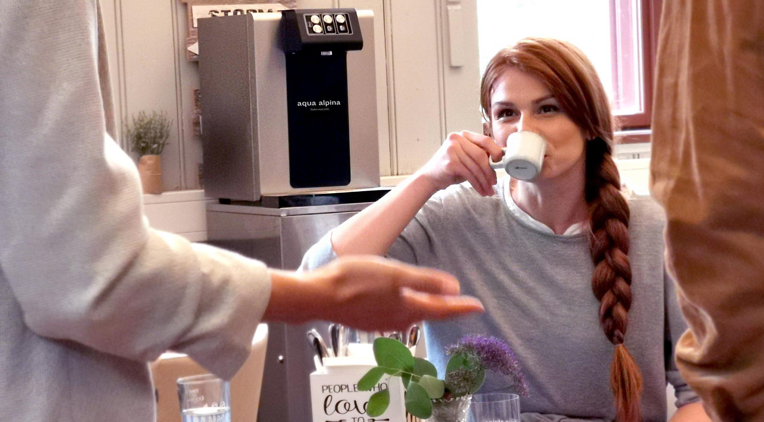 Frau sitzt mit Kaffee vor Wasserspender Soda Premium