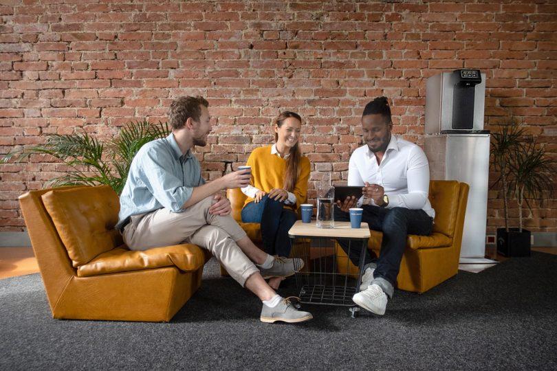 Personen Sitzen Lachend Zusammen Mit Sodawasserspender Im Hintergrund