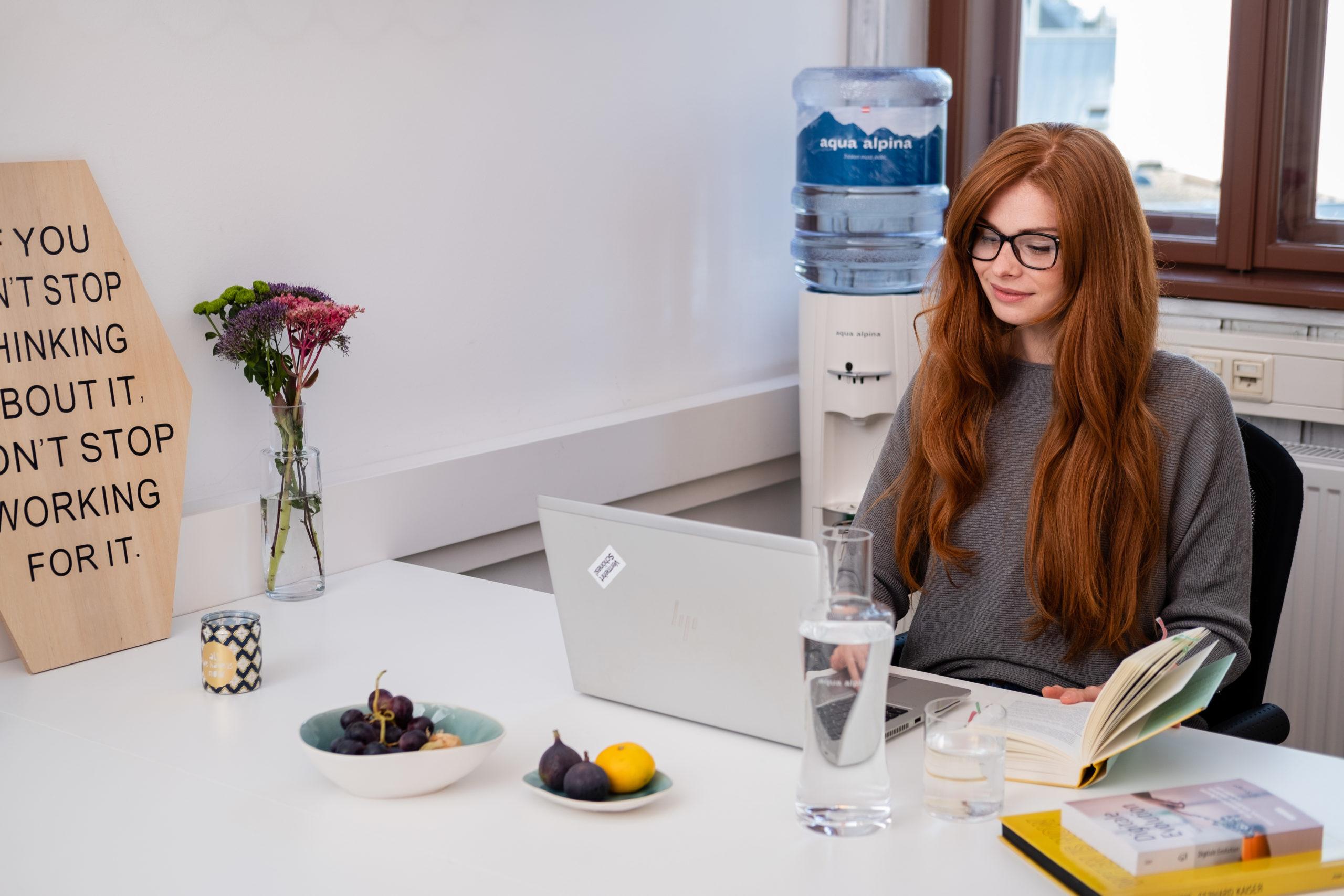 Frau Mit Roten Haaren Im Büro Mit Wasserspender Im Hintergrund
